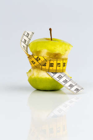 cinta metrica: manzana con una cinta métrica. Foto simbólica para la dieta y, dieta saludable rica en vitaminas.