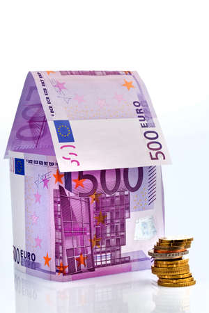 seem: a house built with money seem € on a white background. building savings, house building and home buying.