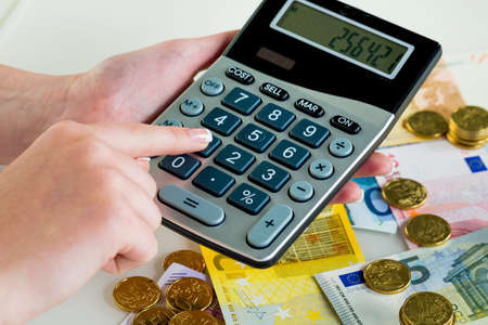 accounted for: hand with calculator and bills. symbolic photo for sales, profits, taxes, and costing