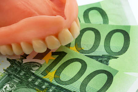 surgery expenses: denture and euro notes, symbolic photograph of dentures, treatment costs and payment Stock Photo