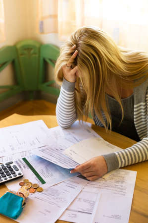existential: a woman with unpaid bills has many debts. unemployment and personal bankruptcy Stock Photo