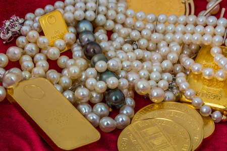 wealth: gold in coins and bars with decorations on red velvet. photo icon for wealth, luxury, wealth tax. Stock Photo