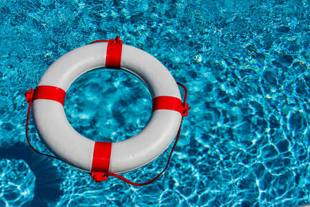 crisis management: an emergency tire floating in a swimming pool. symbolic photo for rescue and crisis management in the financial crisis and banking crisis. Stock Photo
