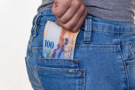the hand of a young woman pulling a swiss franc bill from his pocket of her jeans