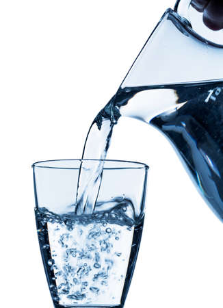 emptied: pure water is emptied into a glass of water from a jug. fresh drinking water