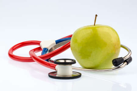 stethoskope: an apple and a stethoscope with a doctor. symbolic photo for healthy and vitamin-rich diet. Stock Photo