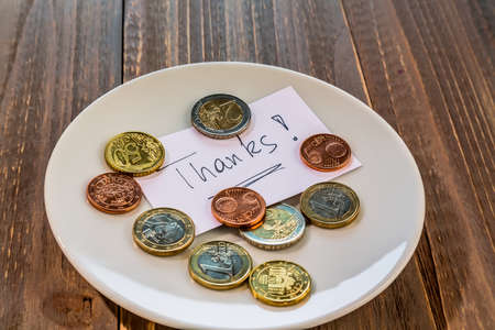 tax tips: a plate of coins for a tip or fee toilets. in english