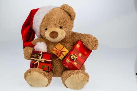 birretes: un oso de peluche con los regalos para la Navidad. vestidos como Santa Claus.