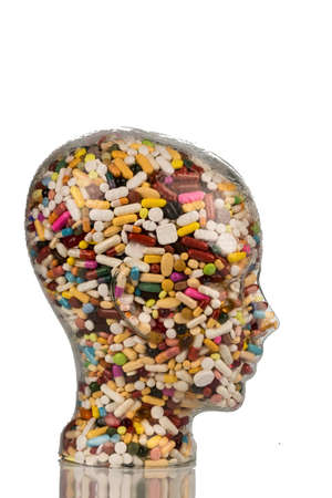 painkillers: a head made of glass filled with many tablets. photo icon for drugs abuse and painkillers.