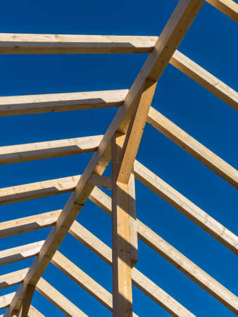 financed: in one house a new roof is being built on a construction site. cleats, wood for roof trusses. Stock Photo