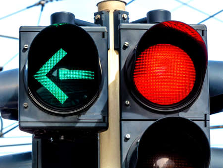 standstill: a traffic light with retoem light. green light for traffic turning left.
