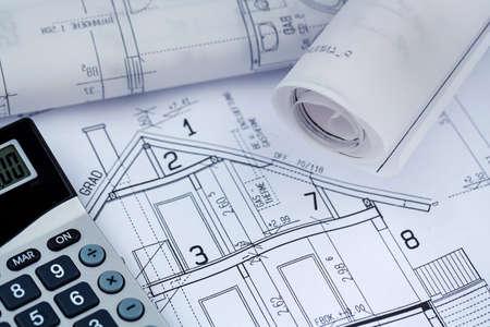 eine Blaupause eines Architekten mit einem Taschenrechner. Symbolfoto für die Finanzierung und Planung eines neuen Hauses. Lizenzfreie Bilder