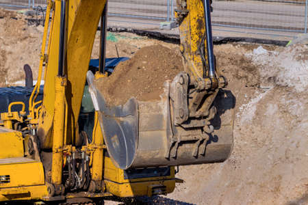 civil construction: excavator on a construction site. excavator bucket with soil, earthworks. Stock Photo