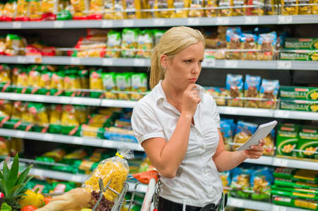cope: a woman is unable to cope with the large selection in a supermarket when shopping. Stock Photo