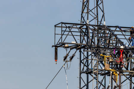 energy needs: construction of a new high-voltage line. workers on electricity poles