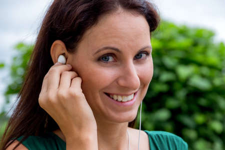 hark: a young woman listening to music on mobile phone to relax Stock Photo