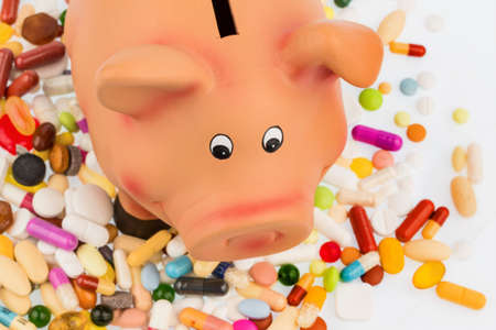 cost: tablets lying next to a piggy bank. symbol photo for costs in medicine and pharmaceutical industry