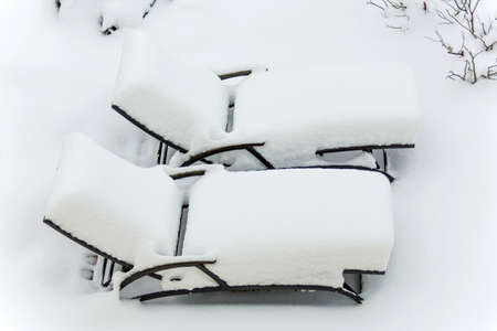 holidays vacancy: snowy garden furniture, symbolfoto for restaurants and hotels during the winter, low occupancy