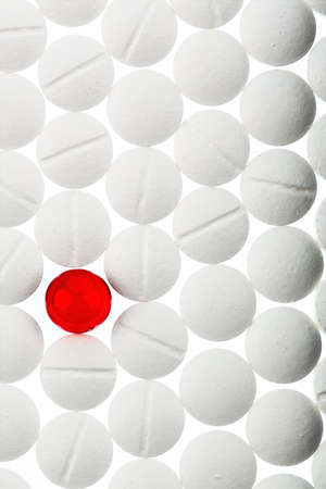 therapie: white tablets in contrast with a red tablet, symbol photo for bullying and individuality