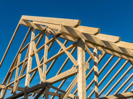 construction industry: in one house a new roof is being built on a construction site. cleats, wood for roof trusses. Stock Photo