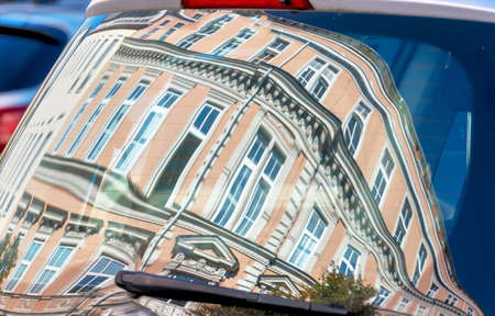 refurbished: beautiful, old houses are reflected in the windows of a car