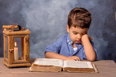 pobre: niño pequeño con el libro y la linterna, símbolo de la educación, la reforma de la educación, el aprendizaje