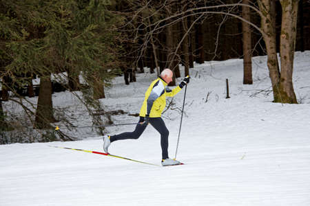 freetime activity: senior in winter on snow while cross-country skis