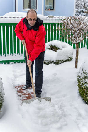 obligations: a man shoveling snow from a new way. onset of winter Stock Photo