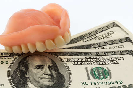 surgery expenses: dentures and dollar bills symbol photo for dentures, treatment costs and payment
