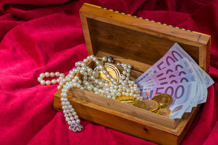 inheritance: gold in coins and bars with decorations on red velvet. photo icon for wealth, luxury, wealth tax. Stock Photo