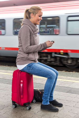 roaming: a young woman waiting for a train and writes with her cell phone a sms Stock Photo