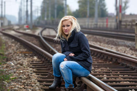 existential: a young woman is sad, anxious and depressed. sits on a track and is lonely Stock Photo