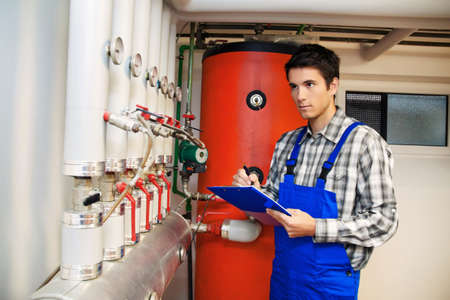 energy costs: young heating engineer in a boiler room for heating system Stock Photo