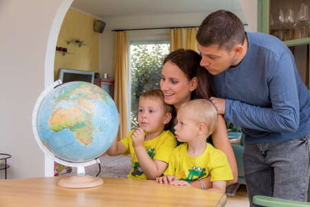 internationally: a family sitting at a globe and planning a trip in the holidays