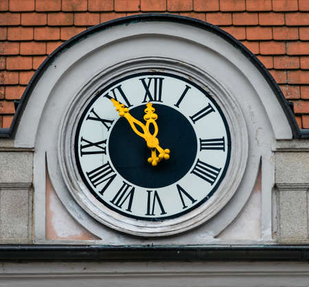 constraints: clock on the facade, symbol of an empty treasury in municipalities and communities. 5vor12 for municipal budget Stock Photo