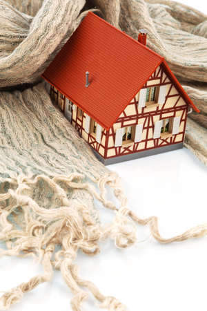 immobilien: a model house is wrapped in a scarf. symbolic photo for thermal insulation and reduce heating costs.