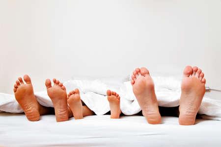 pies: las plantas de los pies de una familia en la cama bajo las sábanas. Foto de archivo