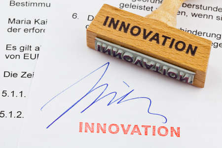 norm: a stamp made of wood lying on a document. german inscription: innovation Stock Photo