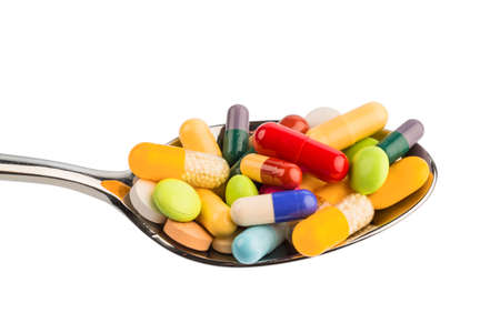 investigated: many colorful pills on a spoon. photo icon for tablets addiction and misuse of drugs.
