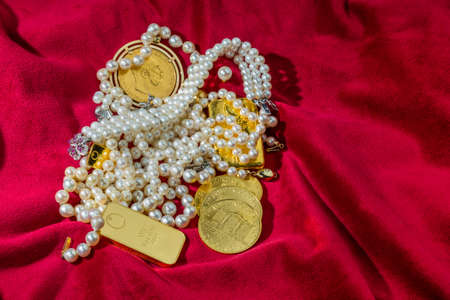 assessment system: gold in coins and bars with decorations on red velvet. photo icon for wealth, luxury, wealth tax. Stock Photo