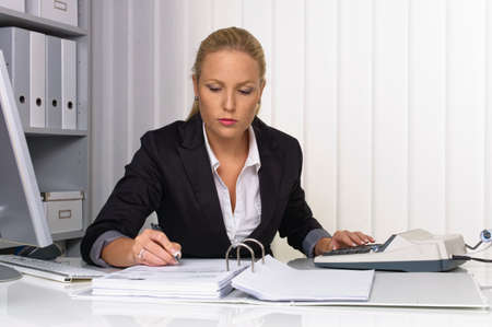 auditors: an accountant at work in the office with calculator