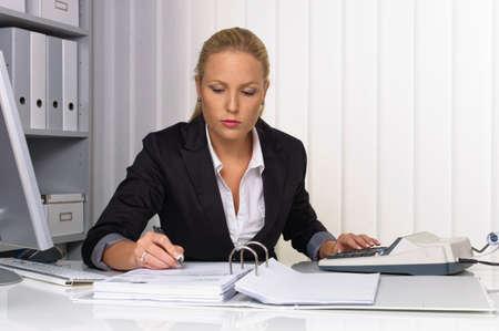 ingresos: un contador en el trabajo en la oficina con la calculadora