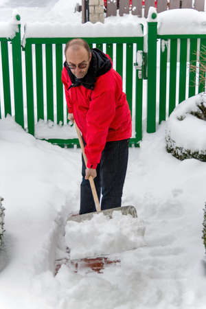 shoveling: a man shoveling snow from a new way. onset of winter Stock Photo