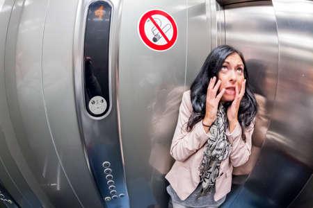 eine junge Frau mit Platzangst in einem Aufzug