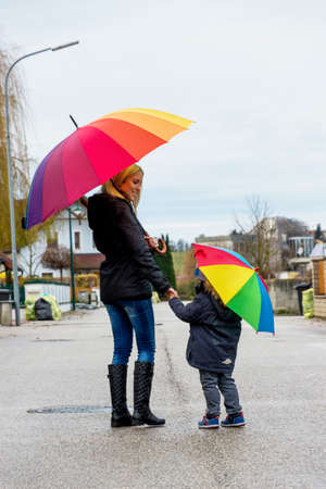 mother and child with umbrella, a symbol of solidarity, assistance, bailout, bailout