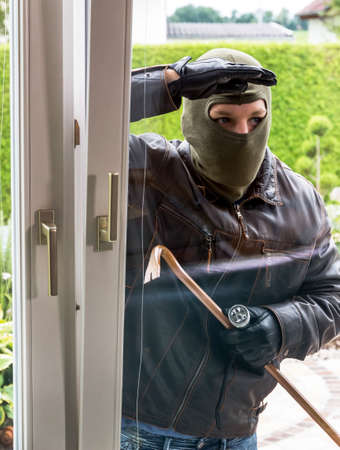 criminal case: a burglar attempts at an open window with a crowbar break