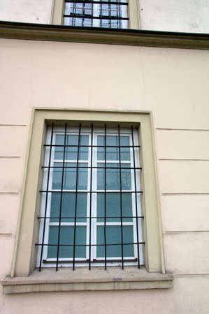 remand: barred windows in a building. symbol image for detention, imprisonment and crime