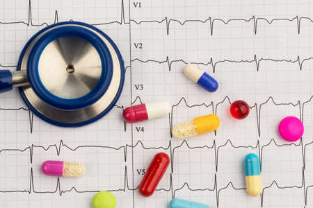 ekg: several tablets lie on an ekg. symbolic photo for diseases of heart and circulation Stock Photo