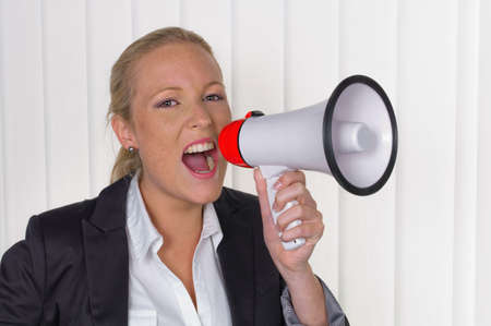 making an announcement: a young business woman with a megaphone making an announcement