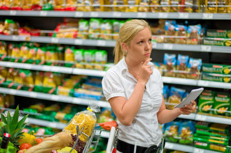 grocers: a woman is unable to cope with the large selection in a supermarket when shopping. Stock Photo